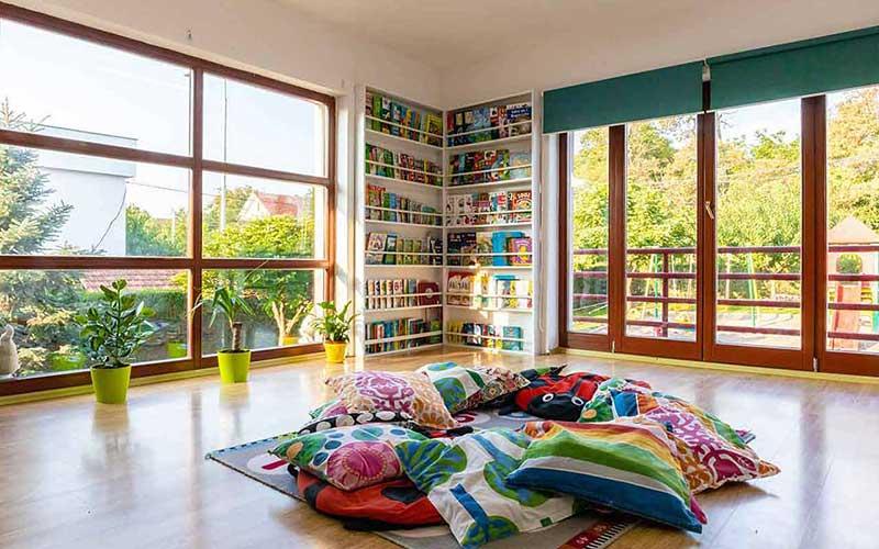 Dhome aktivitetesh ne Kids academy me dritare te medha e plot drite. Jastek per ulje ne mes.