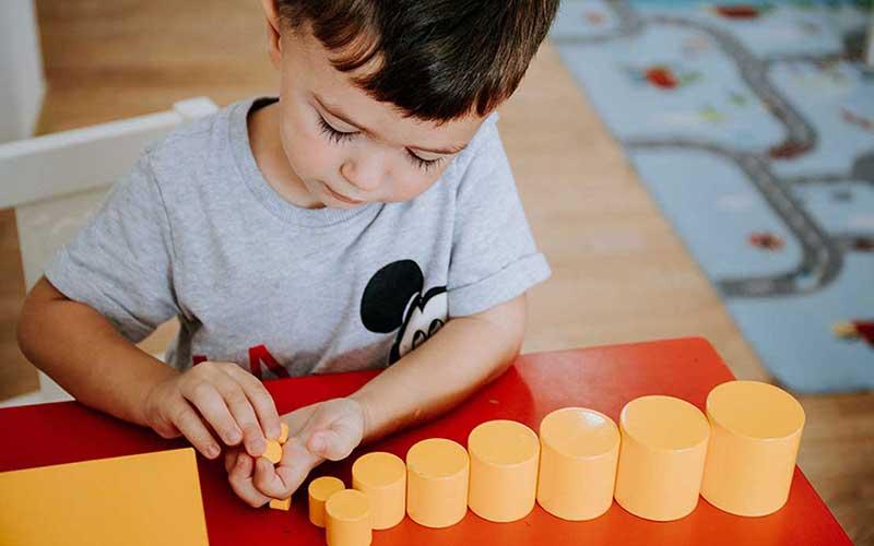 Nxenes i moshes 2-3 vjec i angazhuar ne aktivitet me cilindra Montessori.